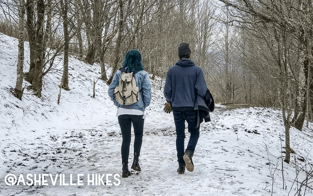 A young couple enjoying a winter hike along a snow-covered trail.