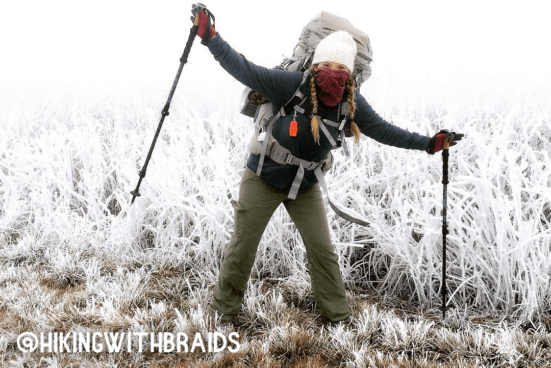 A woman excitedly bundled up for a winter hike.
