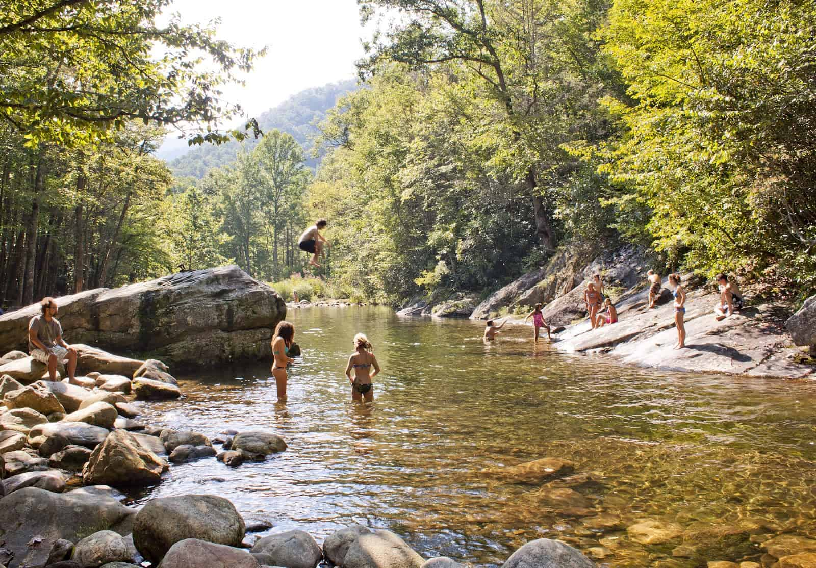 People jumping into river at Sunburst Swimming Hole