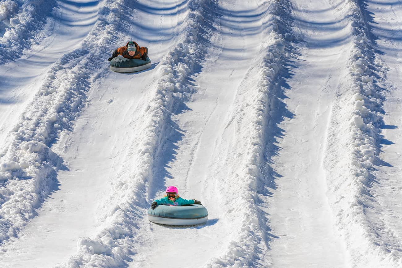 A father and daughter enjoying a snow tubing run at Tube World in Maggie Valley, North Carolina.