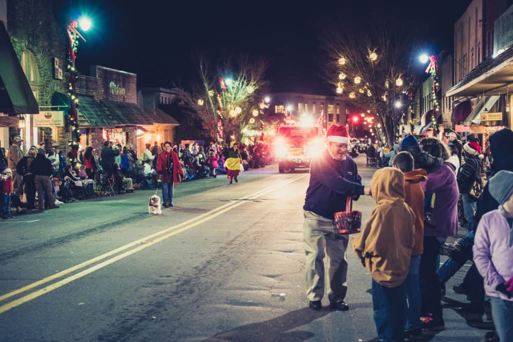 Man handing out candy at the Waynesville Christmas Parade