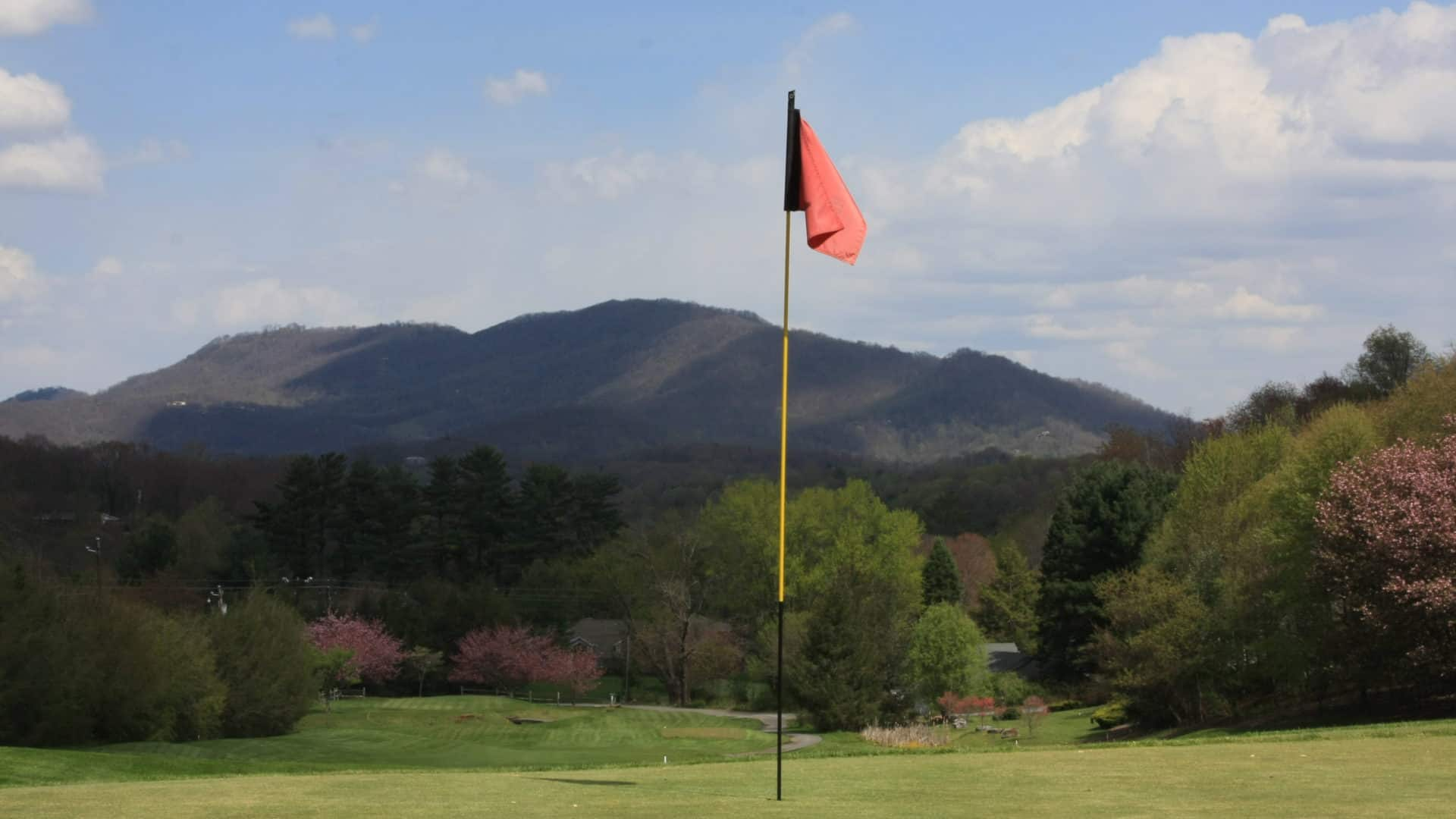 Golf hole with a picturesque mountain backdrop.