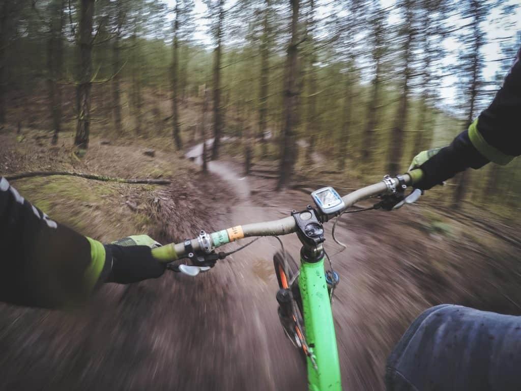 Motion blur of a mountain biker riding down a trail.