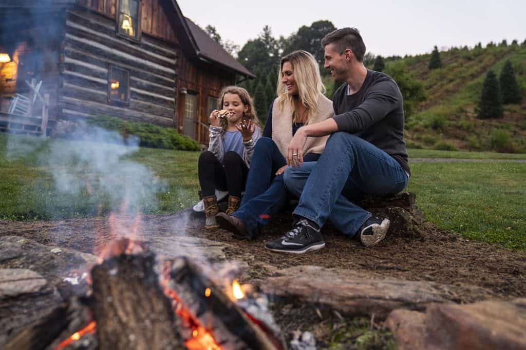 Family sitting by a bonfire at Boyd Mountain Cabins in Waynesville, NC