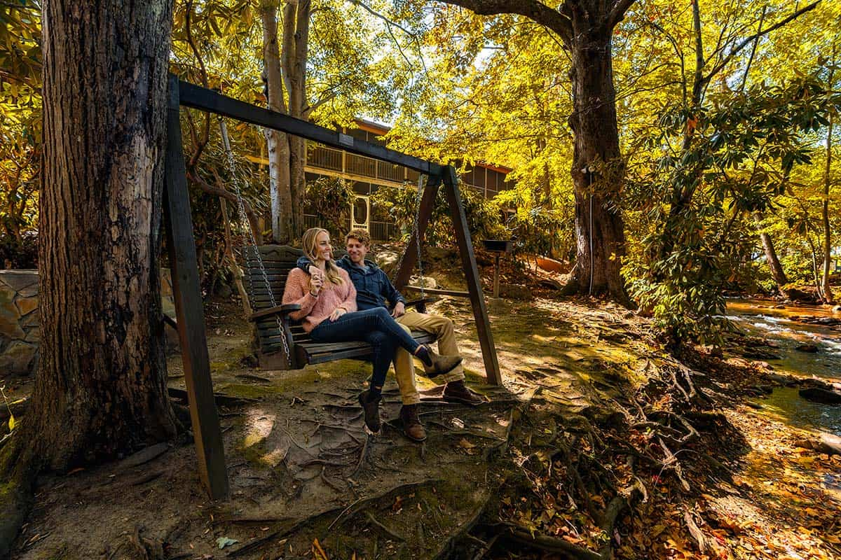 Couple sitting creekside at Jonathon Creek Inn in Maggie Valley, NC