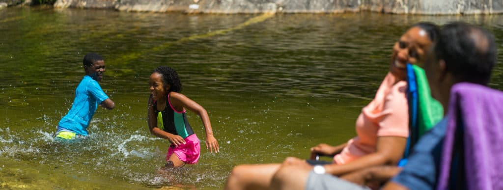 Kids splashing and having fun in Sunburst Swimming Hole in NC.