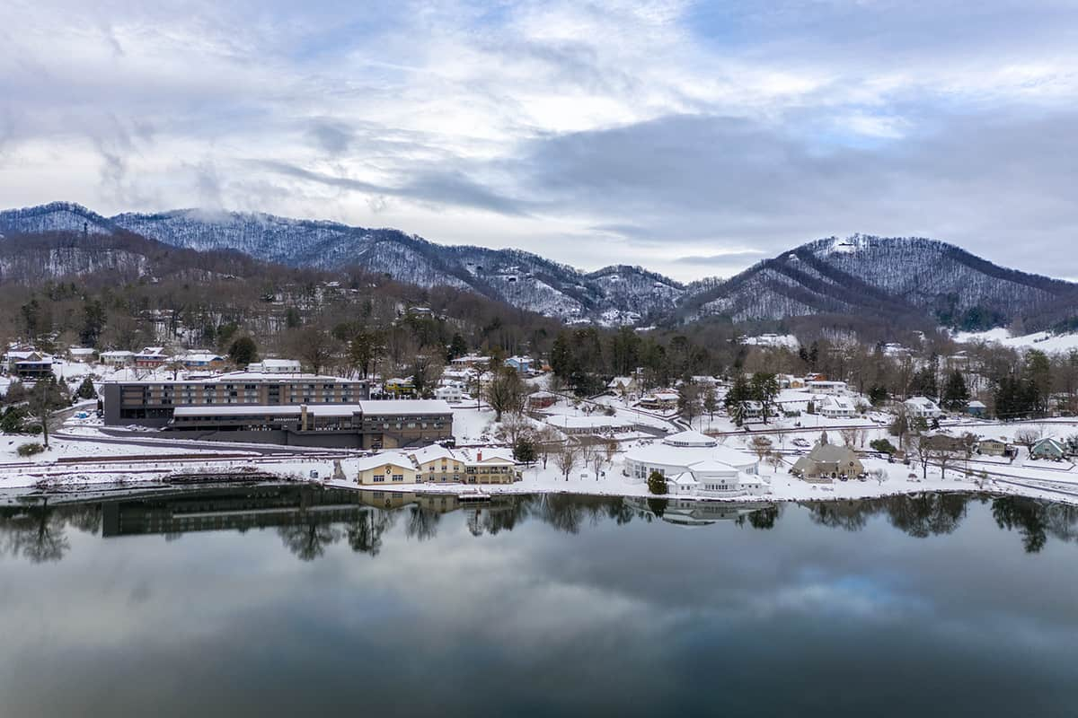 Snow-capped mountains tower in the distance beyond a wintry Lake Junaluska