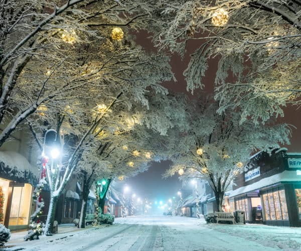 Snow-covered trees adorned with soft-glowing lanterns hang above the icy streets of Downtown Waynesville in the winter.