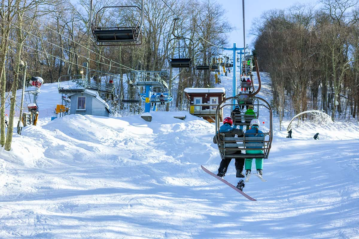 Brother and sister riding the ski lift up to a snowy Cataloochee Valley ski slope on a sunny morning
