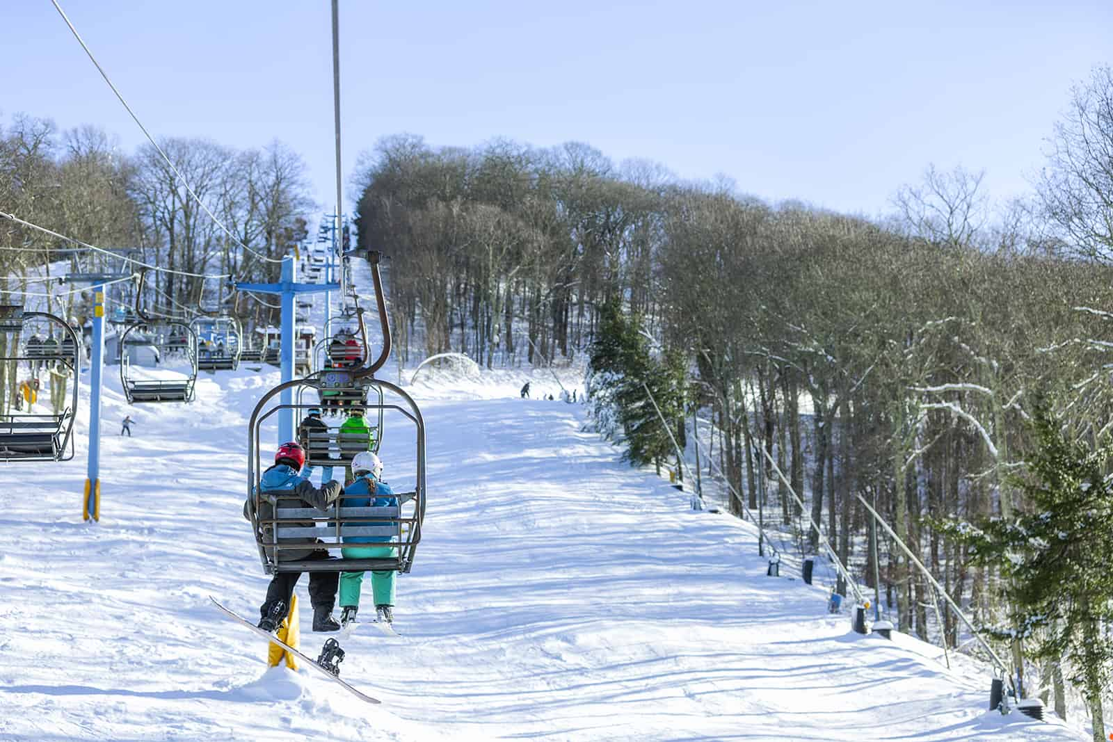 A pair of skiers riding the chairlift up to their slope at Cataloochee Ski Area.